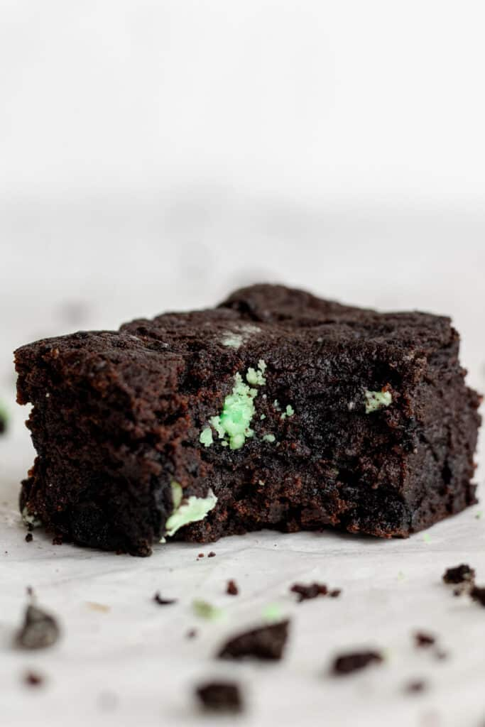 side view of single square cut brownie with a bite into it.