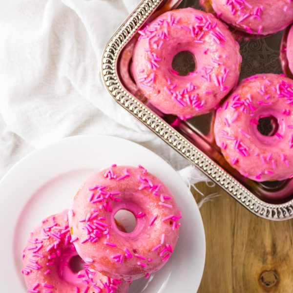 An easy recipe for baked strawberry donuts covered in a pink tinted glaze and sprinkles. It is love at first bite. simplylakita.com #donuts