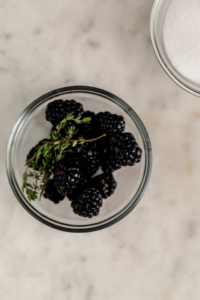 fresh blueberries, thyme, and sugar in small glass bowls