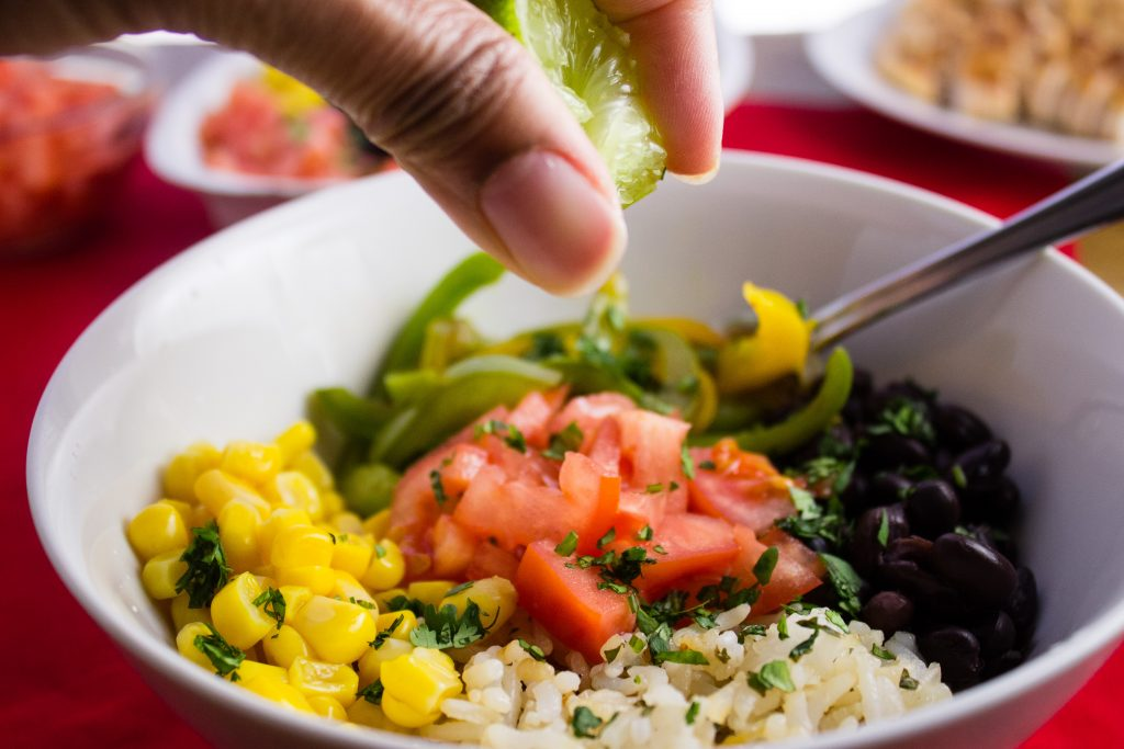 Instead of heading to Chipotle, make this burrito bowl at home instead. Loaded with Cilantro Lime Rice, sauteed bell peppers, chopped tomatoes, and anything else you want. simplylakita.com #chipotle #burritobowl #vegan