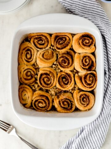 baked sticky buns in white baking dish with striped napkin, fork, and white plates