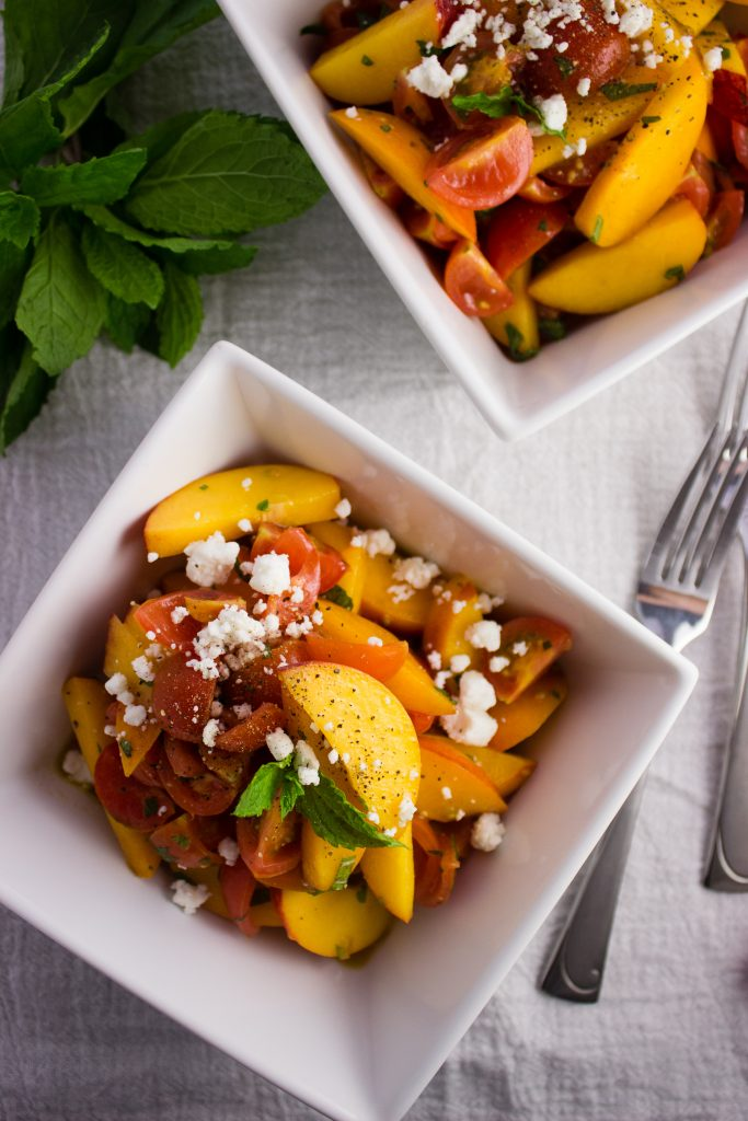 Tomato Peach Salad - A super quick and simple salad made with fresh tomatoes, sliced peaches, mint, a light dressing, and topped with goat cheese. simplylakita.com #healthy #vegan #fresh
