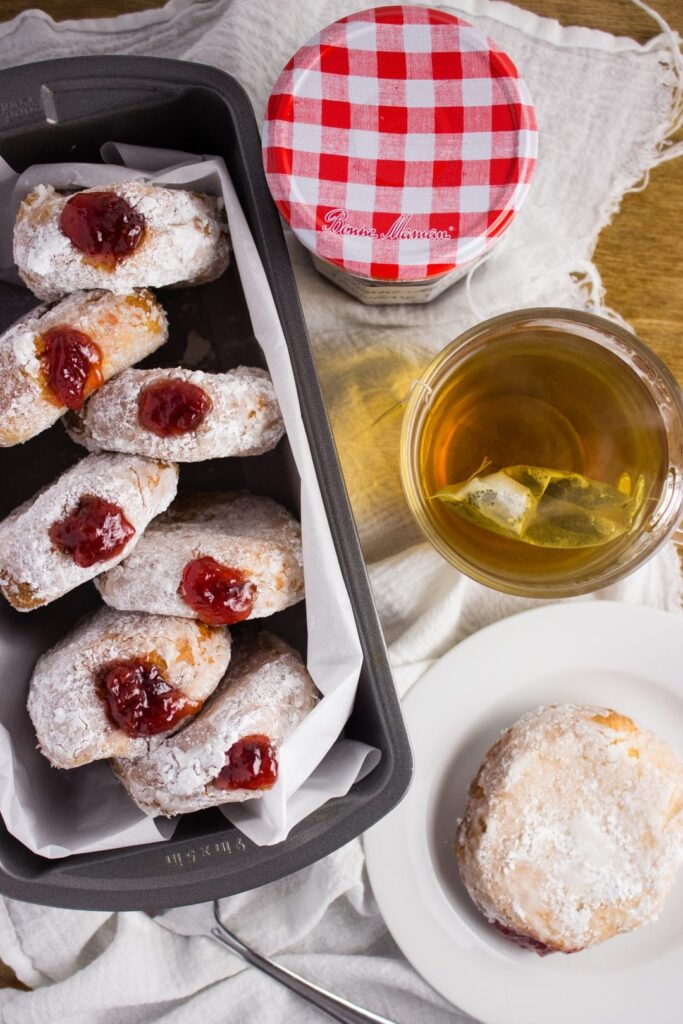 Strawberry Preserves Donuts - Deep fried cake donuts filled with strawberry preserves make the perfect treat to enjoy in bed on Mother's Day with fresh fruit and your favorite cup of coffee. simplylakita.com #donuts #strawberry