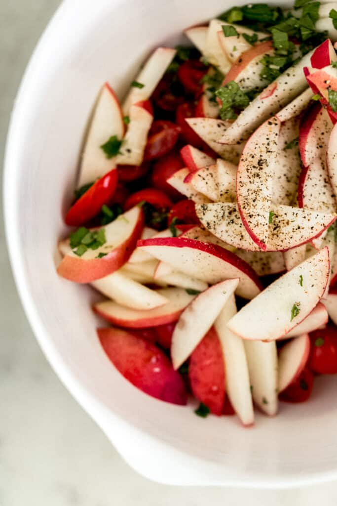 ingredients for tomato peach salad in large white mixing bowl