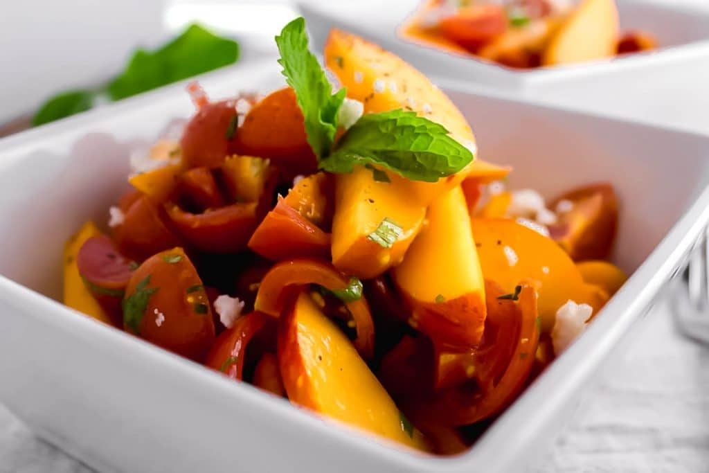 Tomato Peach Salad - A super quick and simple salad made with fresh tomatoes, sliced peaches, mint, a light dressing, and topped with goat cheese. simplylakita.com #peach #healthy #salad