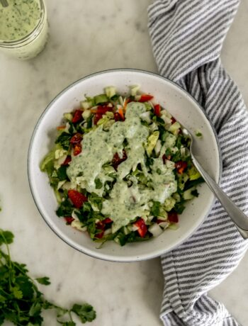 overhead view salad topped with cilantro lime dressing in bowl with fork.