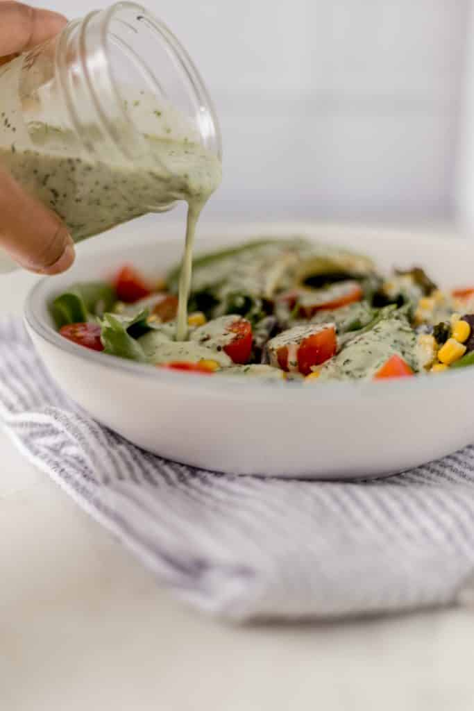 This Cilantro Lime Salad Dressing is the perfect way to top a tex-mex salad with baby spring mix, corn, black beans, tomatoes, and avocado. www.simplylakita.com #salad #healthy