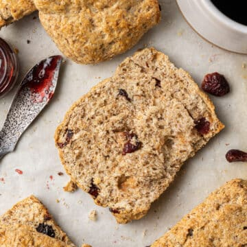 half of flaxseed scone with others around it with spreader and jam.