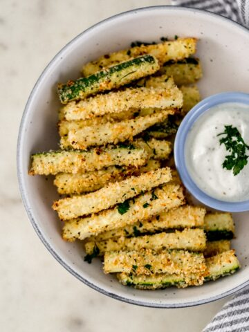 overhead view zucchini fries in serving bowl with small bowl of dipping sauce and cloth napkin