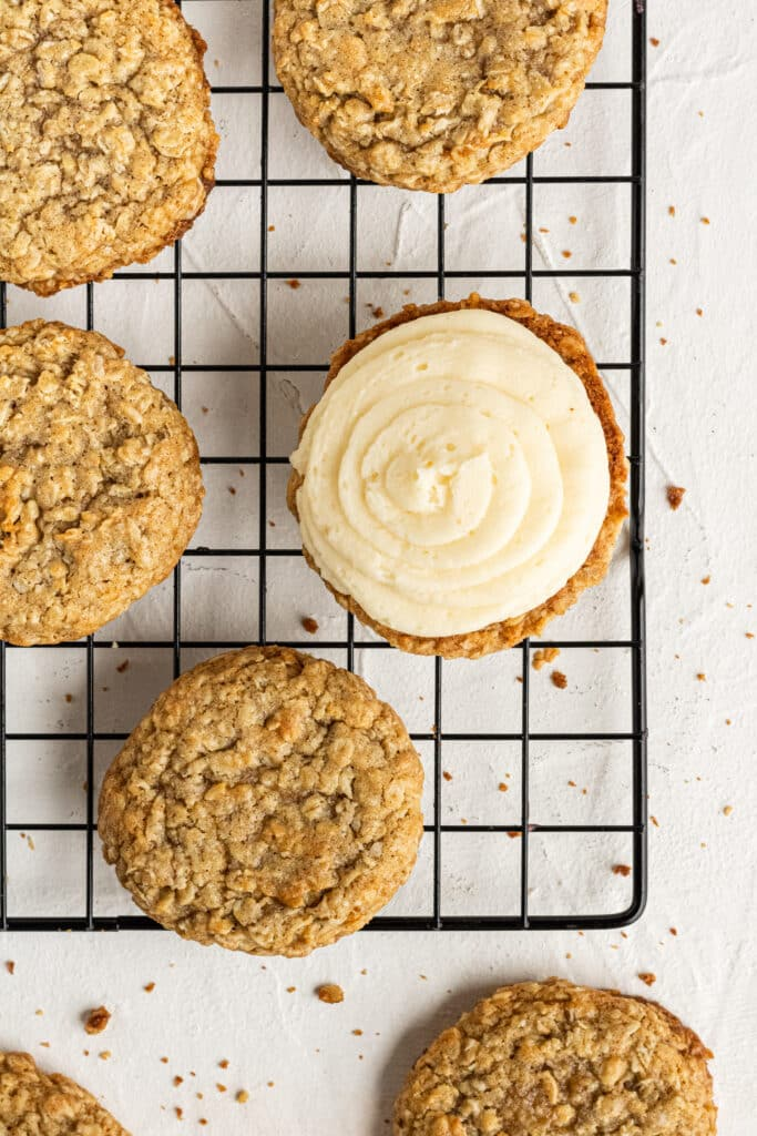 oatmeal cookies on cooling rack with one cookie topped with cream filling.