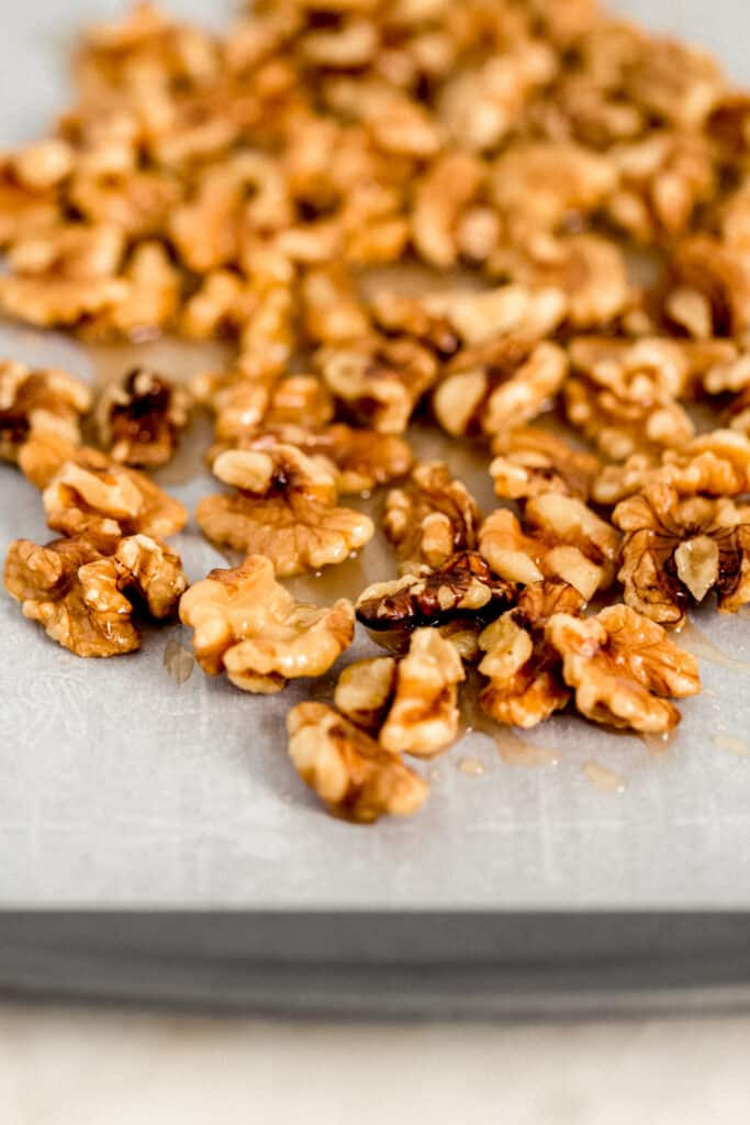 candied walnuts on parchment lined baking sheet.