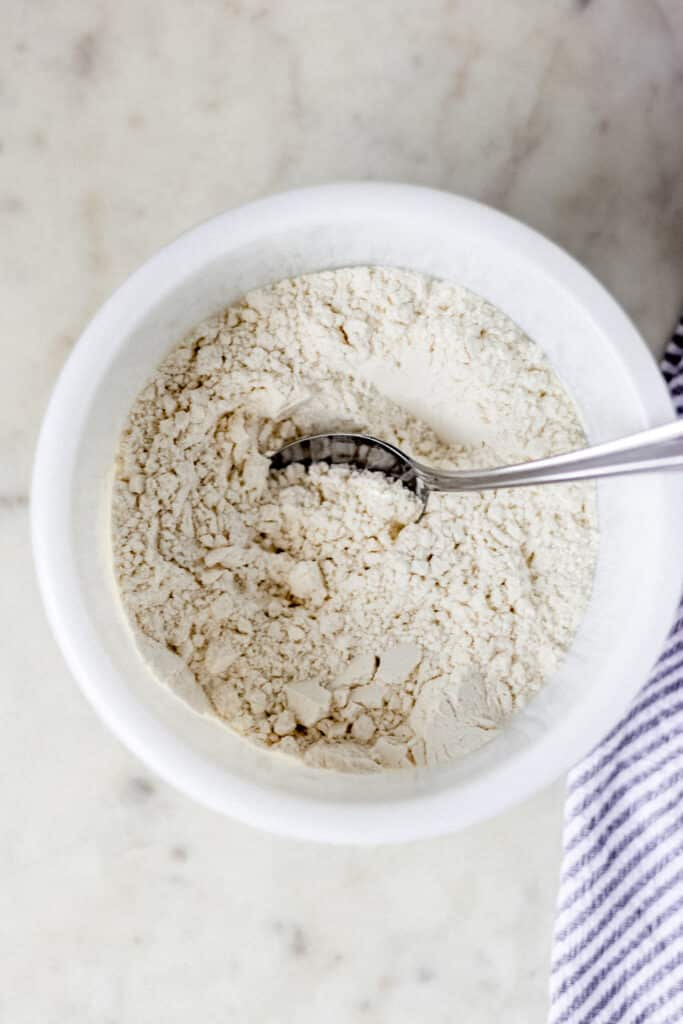 flour, baking soda, and cream of tartar in a white bowl with spoon