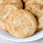 close up side view snickerdoodle cookies on a white plate