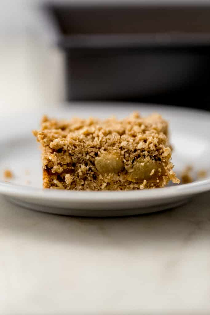 close up view of single apple crumble bar on small white plate.