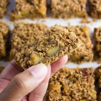 Close-up of hand holding an Apple Crumble Bar with more in the background
