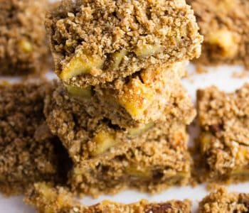 close-up side view Apple Crumble Bars stacked on one another with more in the background