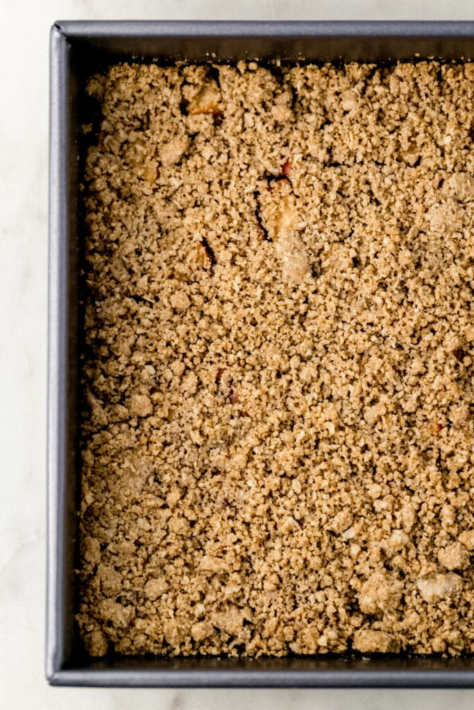 apple crumble bars in a square baking pan before baking.