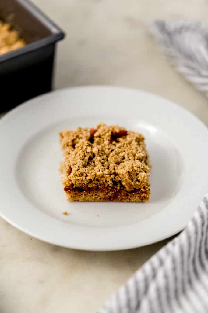square of apple crumble bar on white plate with baking dish in the background.