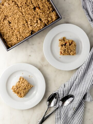 overhead view apple crumble bars in square baking dish and two white plates with spoons and a cloth napkin