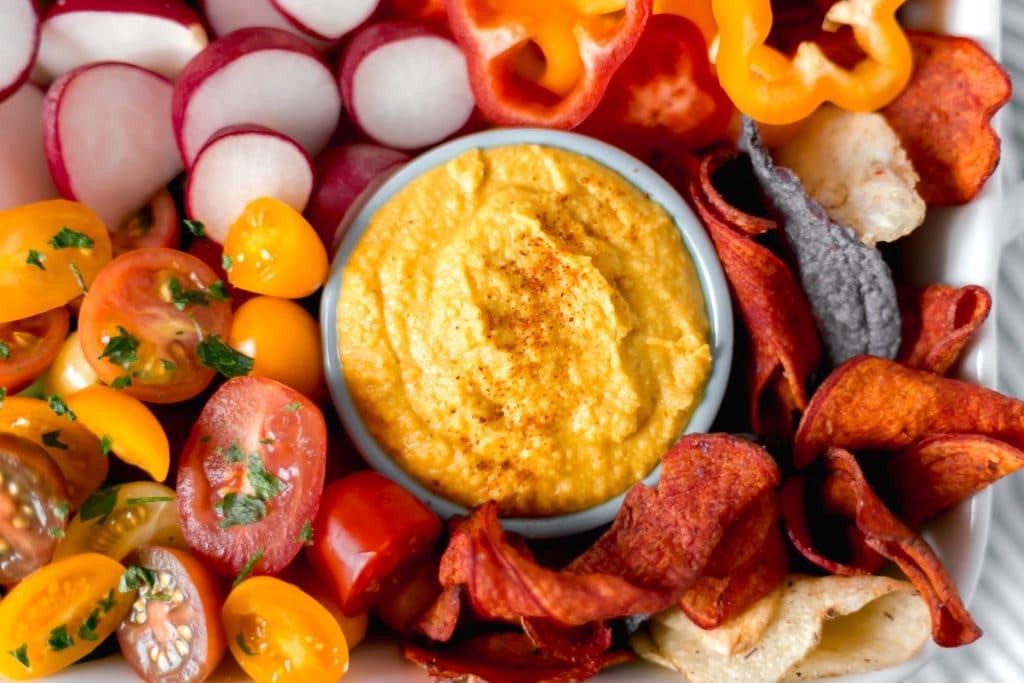 Curry Hummus in small bowl with chips and vegetables