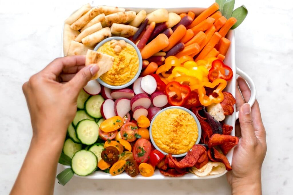 curry hummus with vegetable platter and hands