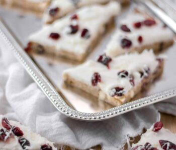 overhead view homemade cranberry bliss bars on silver platter over white napkin