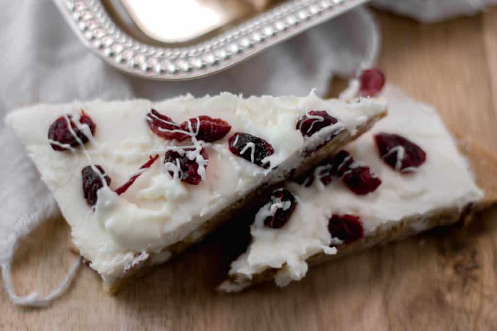 Homemade Cranberry Bliss Bars - A sweet blondie crust topped with a cream cheese frosting. A copycat favorite you can make at home yourself in minutes. simplylakita.com #holiday #starbucks #cranberryblissbars