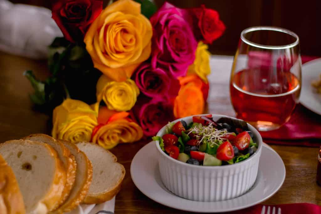 close-up side view bowl of salad on plate with bread, flowers, and wine