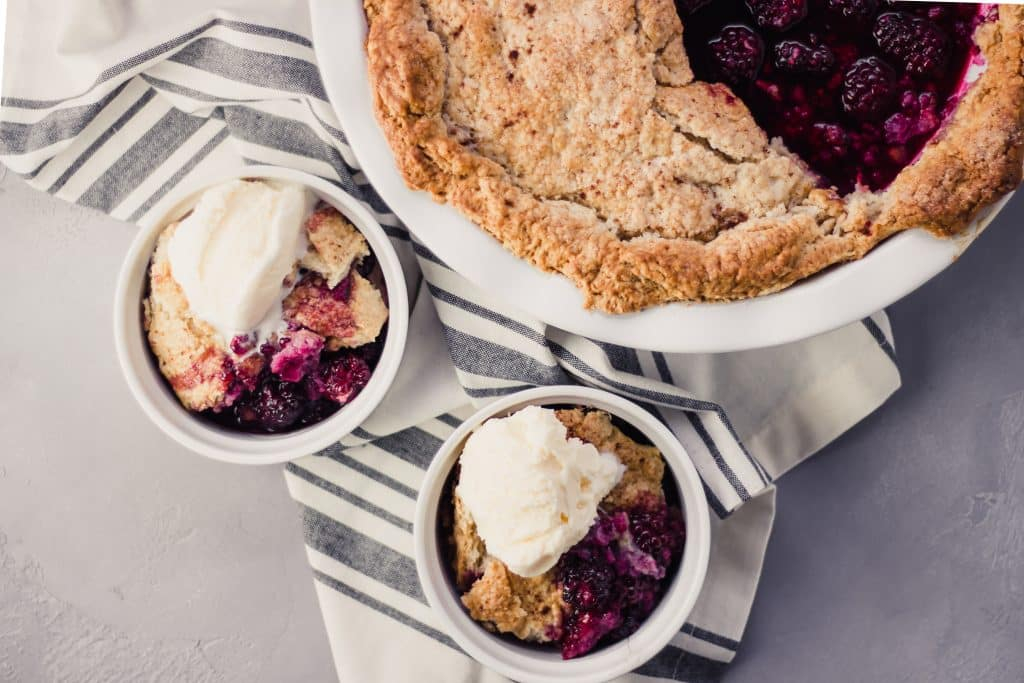 overhead view of Blackberry Cobbler in two bowls and serving dish