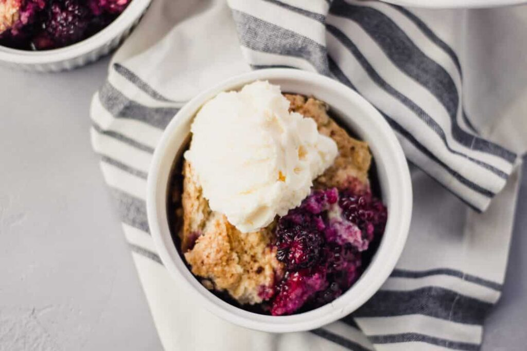 Overhead view Blackberry Cobbler in bowl topped with ice cream