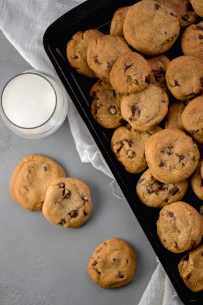 Overhead view Coconut Oil Chocolate Chip Cookies on a sheet pan by a glass of milk