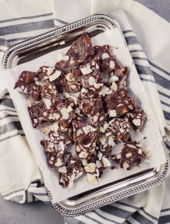 overhead view of trail mix bark on silver tray over napkin