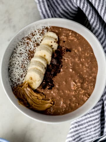 chocolate mocha overnight oats in white bowl topped with banana slices, coconut, peanut butter, and chocolate