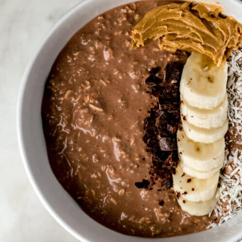 overhead view chocolate mocha overnight oats in white bowl topped with banana slices, coconut, peanut butter, and chocolate