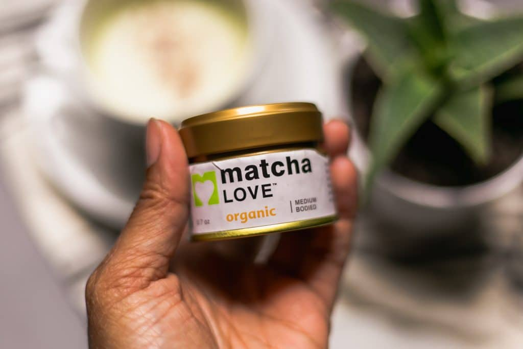 hand holding matcha powder for matcha latte