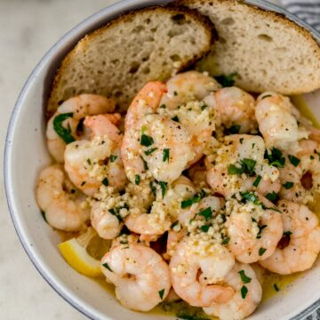 overhead view garlic butter shrimp in white serving bowl with bread and lemon wedges