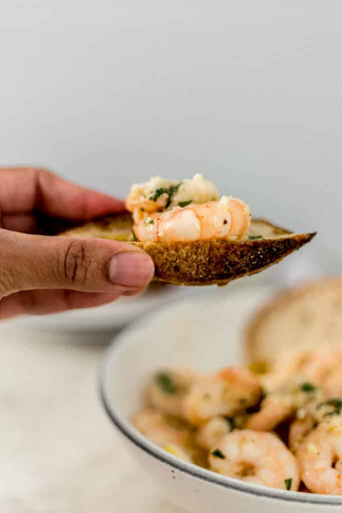 hand holding piece of bread with shrimp on it.
