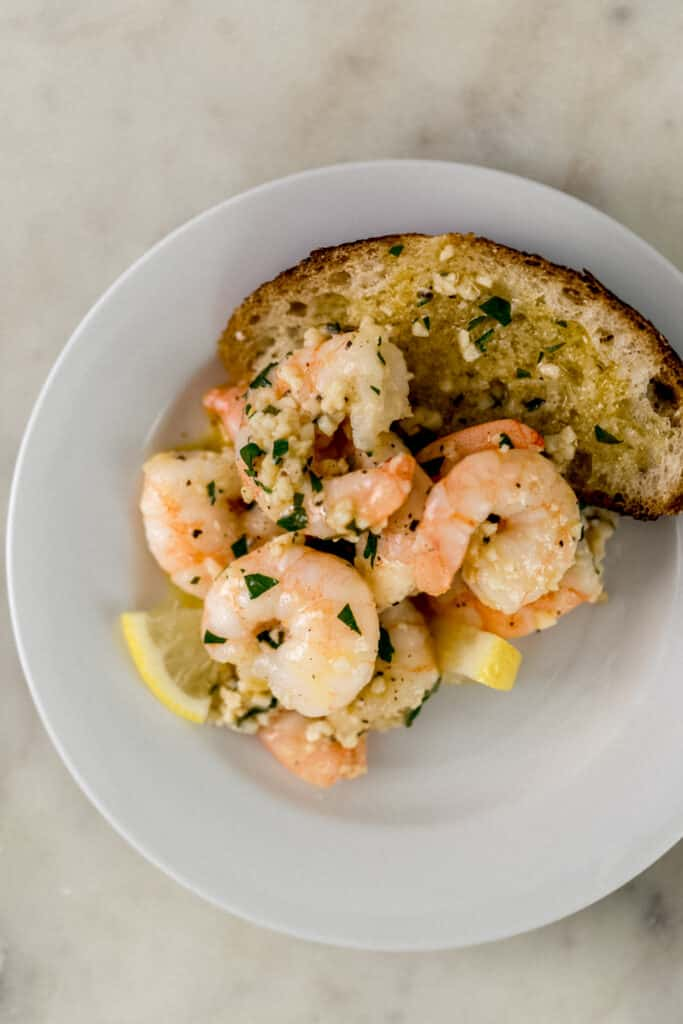 white plate with garlic butter shrimp, lemon, and bread on it.
