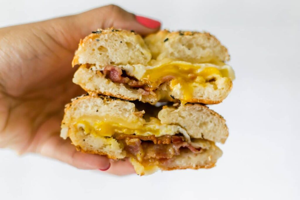 hand holding breakfast bagel sandwich that is cut in half