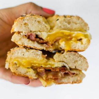 hand holding breakfast bagel sandwich