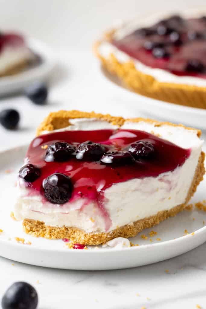 slice of blueberry cheesecake on white plate with a bite out of it.