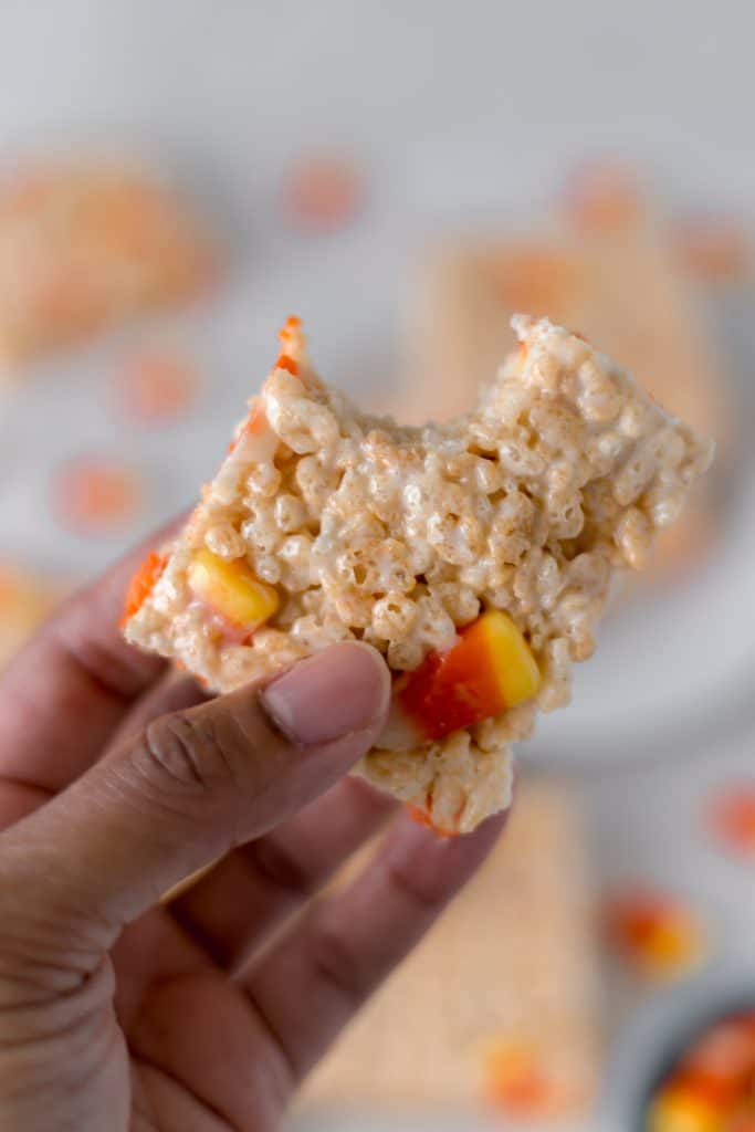 Hand holding a Candy Corn Rice Krispie Treats with a bite in it