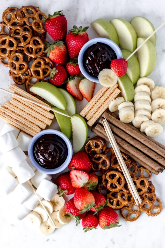 This Epic Dessert Board a is sweet take on the Instagram worthy cheese board. It contains fruit, cookies, marshmallows, and a chocolate dipping sauce. simplylakita.com #dessert #sweets #dessertboard #sweettreats #chocolatesauce