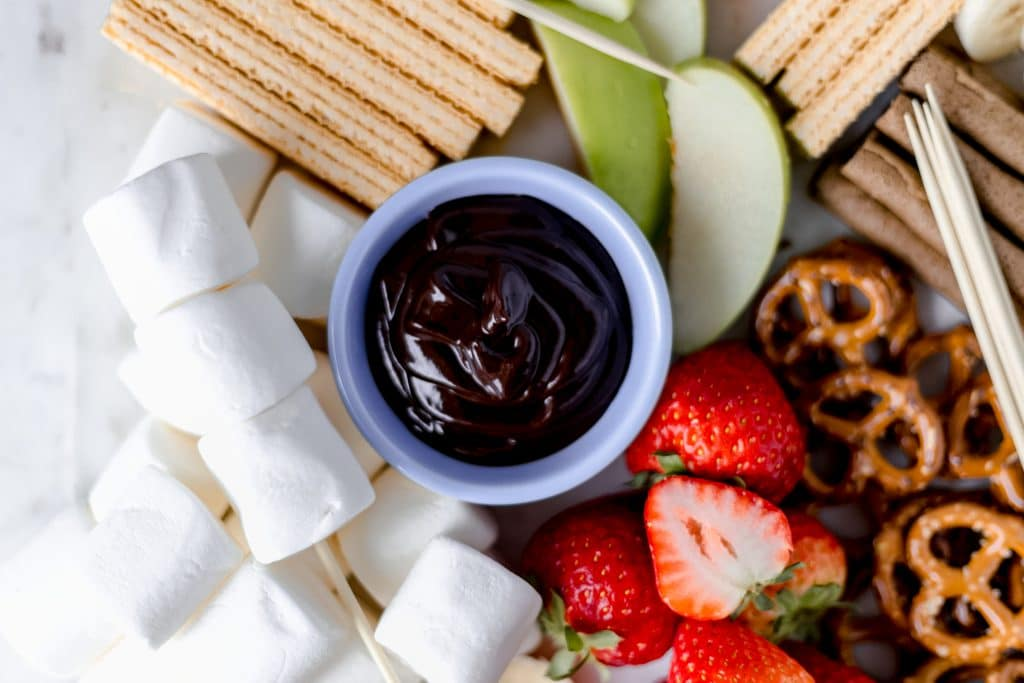 This Epic Dessert Board is a sweet take on the Instagram worthy cheese board. It contains fruit, cookies, marshmallows, and a chocolate dipping sauce. simplylakita.com #dessert #sweets #dessertboard #sweettreats #chocolatesauce