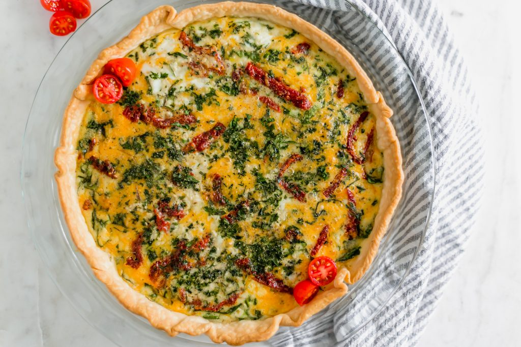 sun dried tomato quiche with a few fresh tomatoes on top