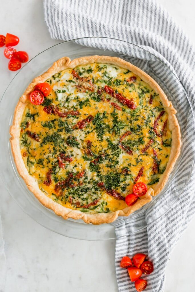 Sun-Dried Tomato Quiche is loaded with eggs, cheddar cheese, spinach, and sun-dried tomatoes. It is easy to make with a premade crust and delicious. simplylakita.com #quiche #easyquicherecipe #breakfast #brunch