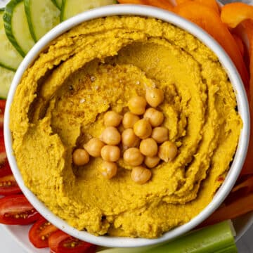 curry hummus in white bowl topped with chickpeas on top of fresh vegetables