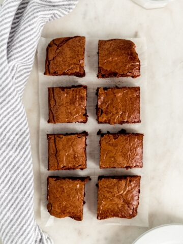 overhead view of brownies cut into 8 square pieces with plates, glass of milk, and cloth napkin