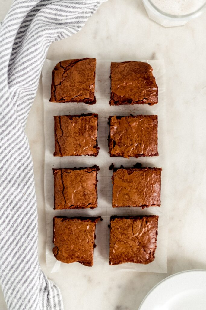 overhead view fudgy brownies cut into 8 squares next to white plates, glass of milk, and cloth napkin.