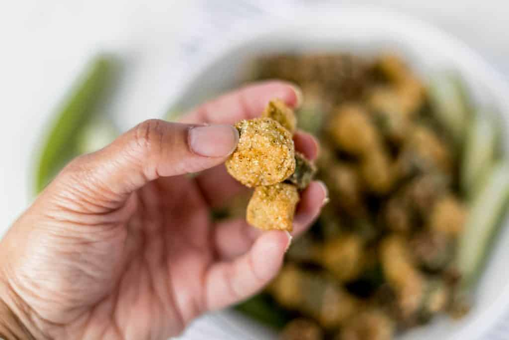 hand holding a few pieces of fried okra